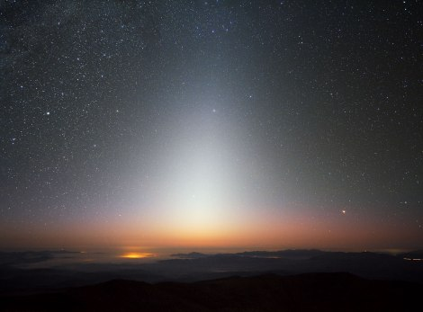 "This image beautifully captures the zodiacal light, a triangular glow seen best in night skies free of overpowering moonlight and light pollution. The photograph was taken at ESO's La Silla Observatory in Chile in September 2009, facing west some minutes after the Sun had set. A sea of clouds has settled in the valley below La Silla, which sits at an altitude of 2400 metres, with lesser peaks and ridges poking through the mist. The zodiacal light is sunlight reflected by dust particles between the Sun and Earth, and is best seen close to sunrise or sunset. As its name implies, this celestial glow appears in the ring of constellations known as the zodiac. These are found along the ecliptic, which is the eastward apparent ""path"" that the Sun traces across Earth's sky."